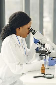 Medisch artsenmeisje die met een microscoop werken. jonge vrouwelijke wetenschapper die vaccinonderzoek doet.