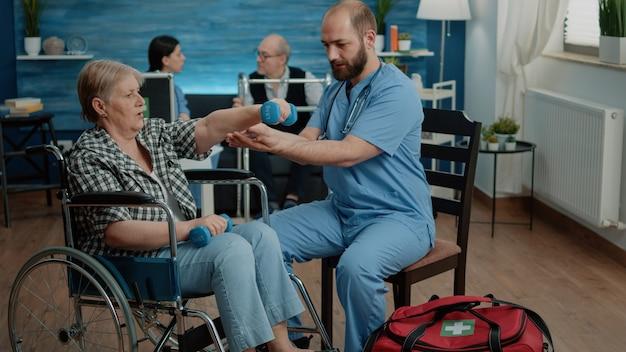 Medisch assistent helpt gehandicapte vrouw met lichamelijke oefeningen
