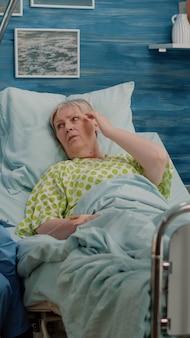 Medisch assistent in gesprek met senior patiënt met ziekte in bed