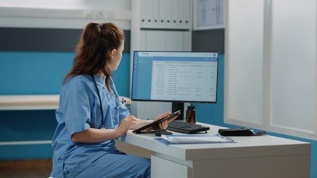Medisch assistent werken met computer en digitale tablet