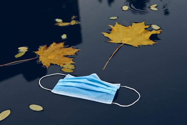 Medisch beschermend gezichtsmasker op de vloer in de straat. verloren gebruikte wegwerp gezichtsmasker op stoep. afval tijdens covid-19.