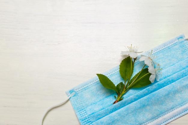 Medisch beschermend masker en knoppen van witte bloemen op een witte muur met kopie ruimte. allergiebescherming