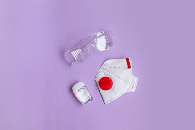 Medisch beschermend masker, gasmasker ffp, antiseptische en beschermende bril liggen op paarse achtergrond. coronavirus pandemie 2019. coronavirus, covid 19 preventie-items.