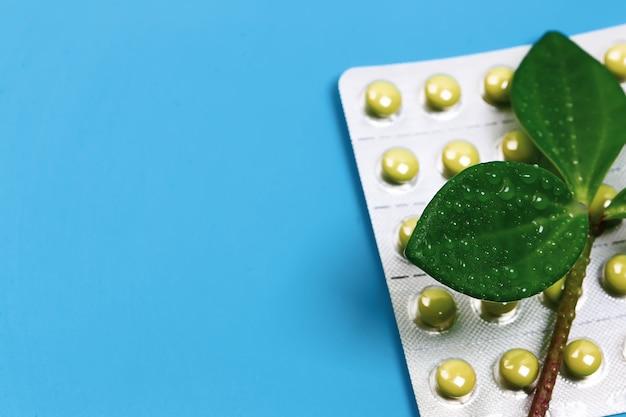 Medisch concept homeopathische geneeskunde op een blauwe achtergrond tabletten met een groene plant lege ruimte boven...