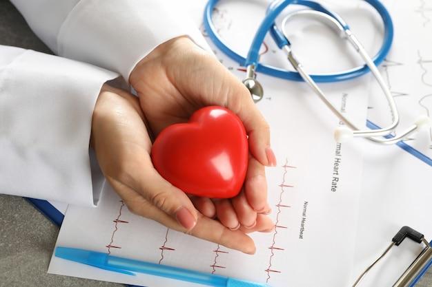 Medisch concept met het vrouwelijke hart van de artsenholding