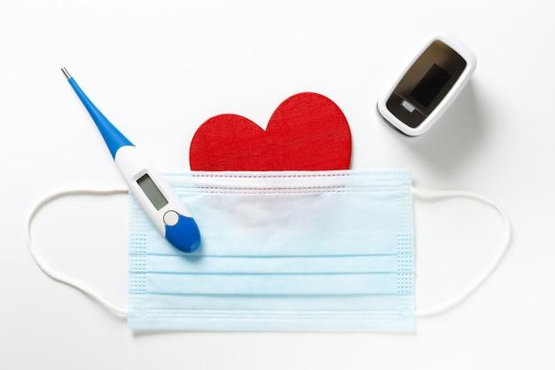 Medisch en covid concept van saint valentine day, rood hartsymbool met geneeskunde beschermingsmasker, pulsoximeter en thermometer op wit