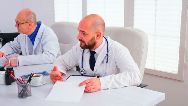 Medisch expert praten over gezondheidszorg tijdens seminar met ziekenhuispersoneel in vergaderruimte wijzend op klembord. kliniektherapeut bespreekt met collega's over ziekte, medisch professional
