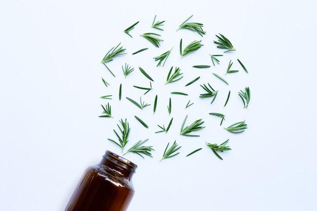 Medisch flessenglas met verse rozemarijnbladeren op wit