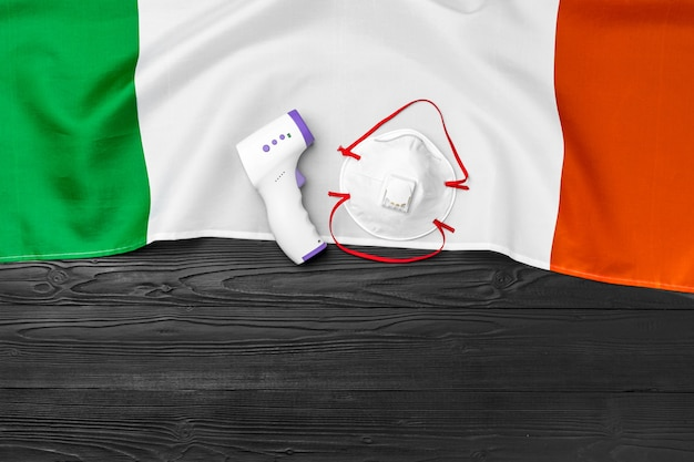 Medisch gezichtsmasker en contactloze thermometer op vlag van italië