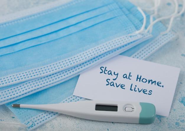Medisch gezichtsmasker met witte kaart en thermometer op blauw. beste bescherming tegen coronavirus, ziektekiemen, bacteriën en virussen. tex op kaart, blijf thuis, red levens.