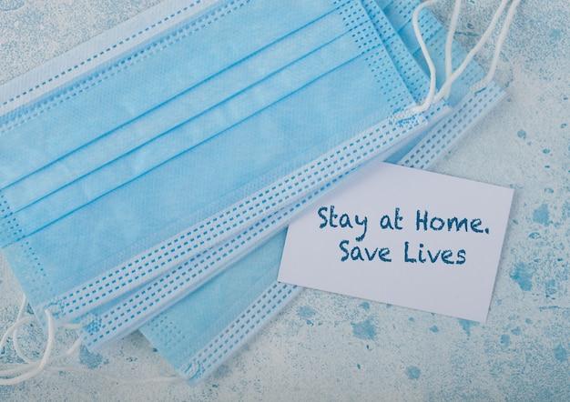 Medisch gezichtsmasker met witte kaart op blauw. beste bescherming tegen coronavirus, ziektekiemen, bacteriën en virussen. tex on card: blijf thuis, red levens.