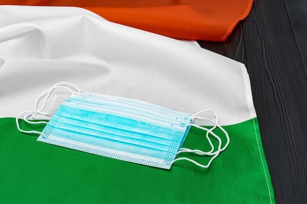 Medisch gezichtsmasker op vlag van italië op een houten bord