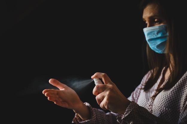 Medisch gezichtsmasker voor meisjes brengt antiseptische gel aan op de zwarte achtergrond van de hand met antibacteriële ontsmettingsmiddel