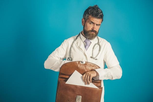 Medisch, kliniek, behandeling en gezondheidszorgconcept - serieuze bebaarde arts met stethoscoop in witte medische toga en aktetas in de hand.