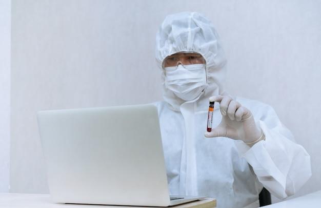 Medisch laboratoriumtechnicus die chemische beschermende kleding draagt en covid-19 positieve bloedmonsterbuis houdt voor test en analyse