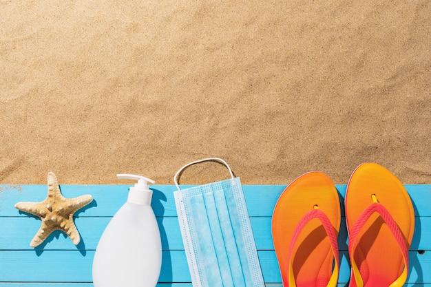 Medisch masker antiseptische strandslippers en zeesterren op een houten mat op een zanderige achtergrond met een concept voor kopieerruimte strandhygiëne