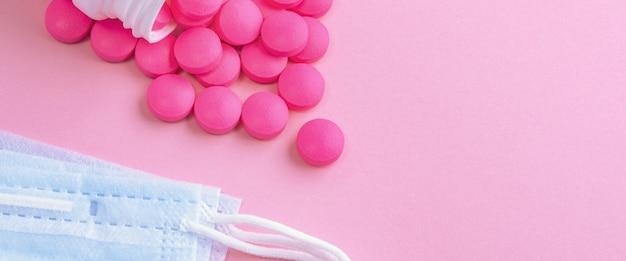 Medisch masker chirurgisch beschermend virus, griep, ziekte en pillen. geïsoleerd op een roze achtergrond.