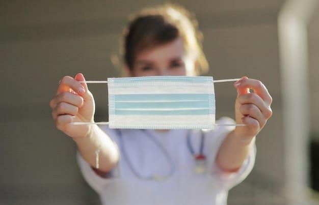Medisch masker dat door een doktersmeisje wordt vastgehouden
