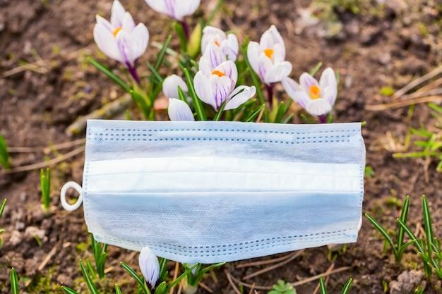Medisch masker dichtbij lentebloemen