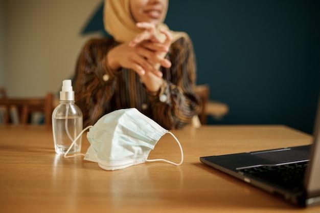 Medisch masker en antiseptisch, arabisch meisje in hijab in universiteitscafé op achtergrond. moslimvrouw met boeken die in bibliotheek zitten.