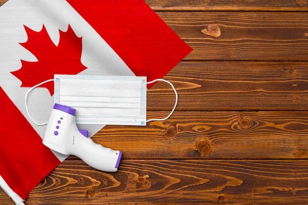 Medisch masker en contactloze thermometer op vlag van canada op een houten bord