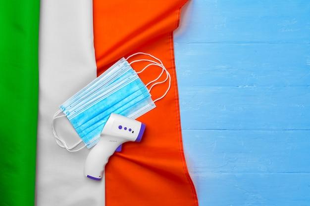 Medisch masker en contactloze thermometer op vlag van italië op blauwe houten achtergrond