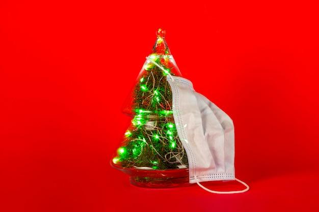 Medisch masker en decoratieve glazen kerstboom op rood