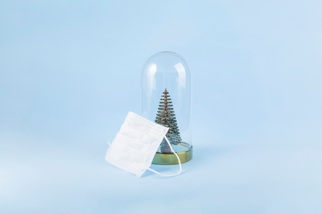Medisch masker en decoratieve kerstboom onder glazen afdekking o