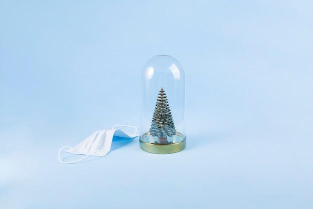 Medisch masker en decoratieve kerstboom onder glazen kap