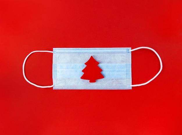 Medisch masker en houten kerstboom op een rode ondergrond