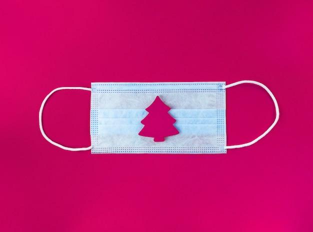 Medisch masker en houten kerstboom