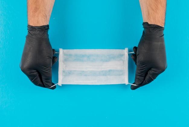 Medisch masker in handen met zwarte handschoenen. bovenaanzicht.