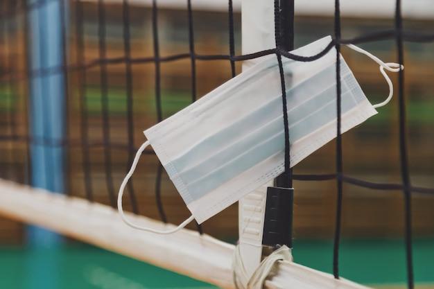 Medisch masker in volleybalnet in een oude lege sporthal met scheidsrechterstoren. achtergrond voor teamvolleybalspel. concept van het krijgen van sport, levensstijl en succes tijdens een periodepandemie. ruimte kopiëren