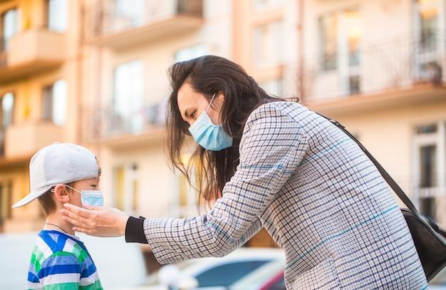 Medisch masker om coronavirus te voorkomen. coronavirus quarantaine. moeder zet een veiligheidsmasker op het gezicht van haar zoon. schooljongen is klaar om naar school te gaan.