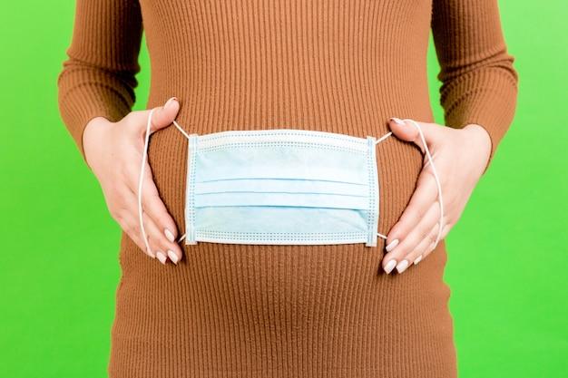 Medisch masker op de buik van een zwangere vrouw, bescherming. concept van virus