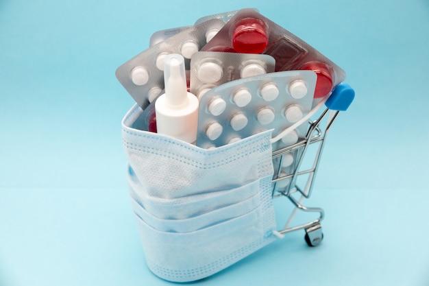 Medisch masker op de kleurrijke geassorteerde pillen patternof geneeskunde pillen kleurrijke geneeskunde op blauwe achtergrond. gezondheidszorg concept