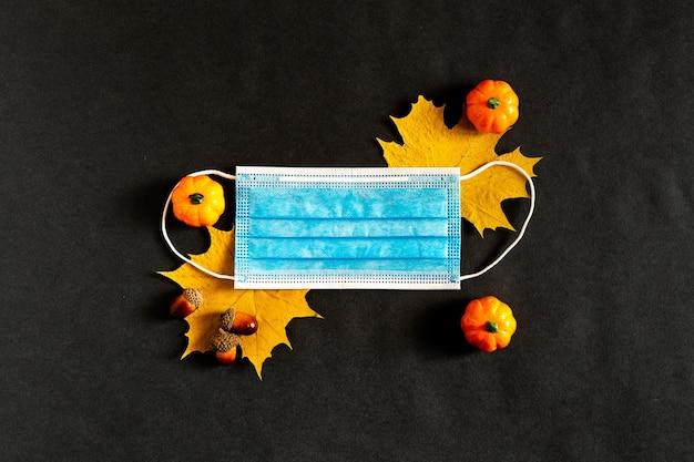 Medisch masker op gele herfst esdoorn bladeren
