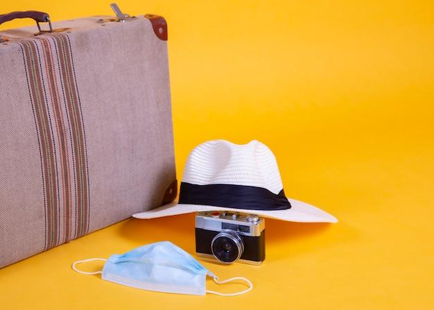 Medisch masker, reizen, vliegtuigen, koffer, camera, gele achtergrond, problemen met reizen door covid-19