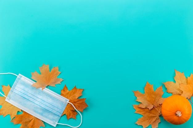 Medisch masker tussen esdoornbladeren. herfstsamenstelling met masker, esdoornbladeren en pompoen.