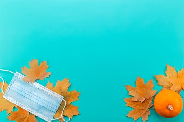 Medisch masker tussen geïsoleerde esdoornbladeren