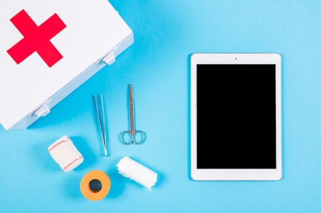 Medisch materiaal met eerste hulpuitrusting en lege digitale tablet op blauwe achtergrond