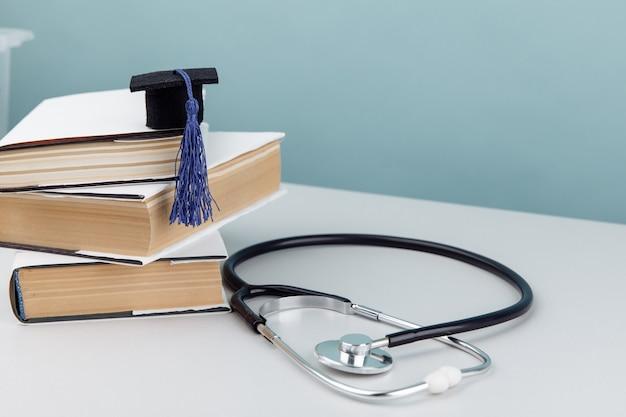 Medisch onderwijs en gezondheidszorg thema. stethoscoop en afstuderen hoed op stapel boeken.