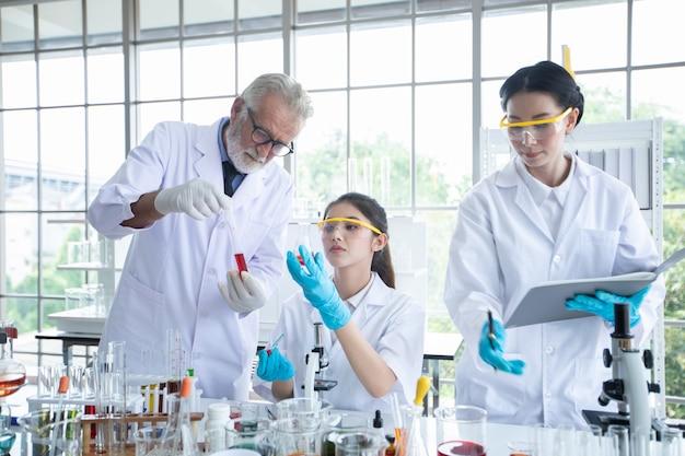 Medisch onderzoek en wetenschappers werken met een microscoop en een tablet en reageerbuisjes,