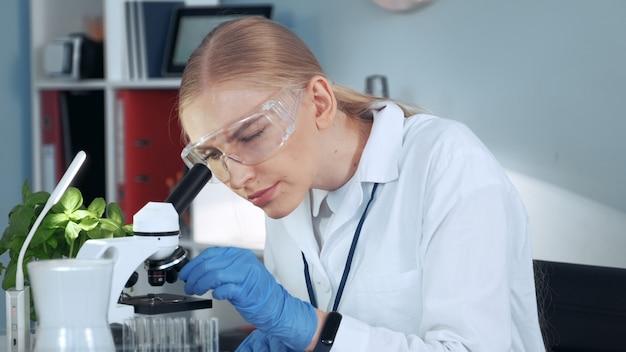 Medisch onderzoeker in veiligheidsbril nemen van monster uit reageerbuis met pipet