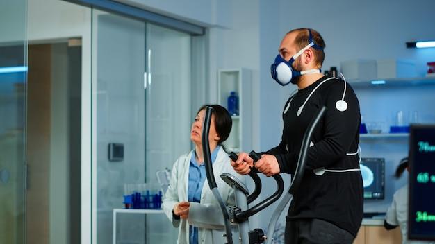 Medisch onderzoeker praat met sportman en toont ecg-scan op virtueel scherm terwijl hij zijn uithoudingsvermogen meet met behulp van lichaamssensoren, elektroden en masker die het hartritme bewaken in het sportwetenschappelijk laboratorium