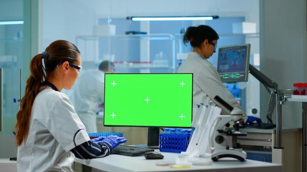 Medisch onderzoekswetenschapper die op pc werkt met een groen scherm mock-up sjabloon in toegepast wetenschappelijk laboratorium. ingenieurs die op de achtergrond experimenten uitvoeren en de evolutie van vaccins onderzoeken met behulp van hightech