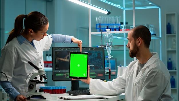Medisch onderzoekswetenschappers met behulp van kladblok met groen scherm mock-up sjabloon in toegepast wetenschappelijk laboratorium wijzend op chroma key display... laboratoriumingenieurs in witte jassen voeren experimenten uit
