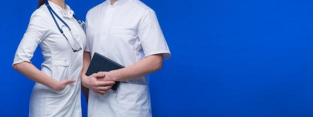 Medisch personeel arts, verpleegster en chirurg met stethoscoop en boek op blauwe achtergrond
