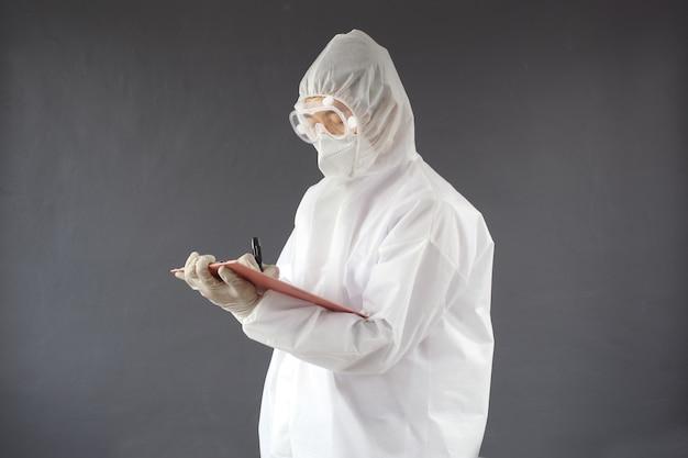 Medisch personeel dat beschermende pbm draagt en patiënt- of diagnostische rapporten schrijft Premium Foto