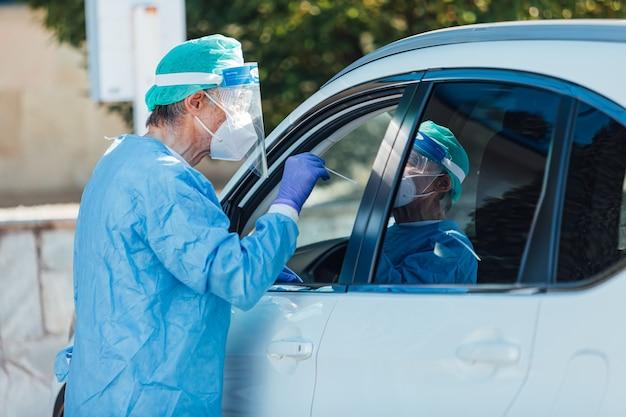 Medisch personeel dat een pbm draagt en pcr uitvoert met een wattenstaafje in de hand, op een patiënt in zijn auto om te detecteren of hij besmet is met covid-19